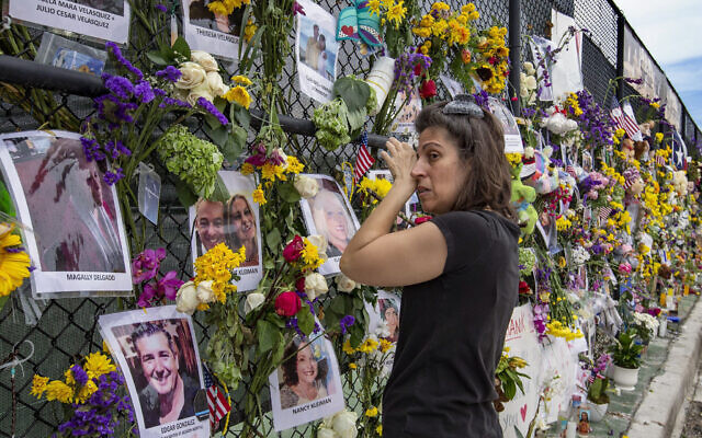 Gini Gonte visits the Surfside Wall of Hope Memorial on Wednesday, July 7, 2021, as she honors her friends Nancy Kress Levin and Jay Kleiman, who lost their lives after the collapse of the Champlain Towers South in Surfside, Fla. (Al Diaz/Miami Herald via AP)