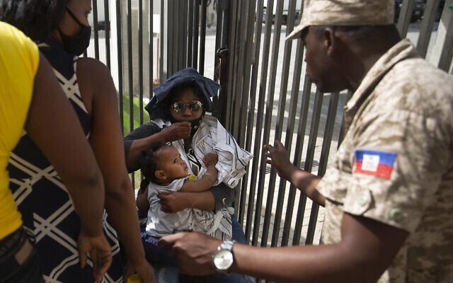 A Haitian police asks a woman to move away from a gate at the U.S. Embassy in Port-au-Prince, Haiti, July 9, 2021. A large crowd gathered outside the embassy amid rumors on radio and social media that the US will be handing out exile and humanitarian visas, two days after Haitian President Jovenel Moise was assassinated in his home. (AP Photo/Joseph Odelyn)