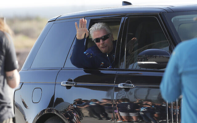 Virgin Galactic founder Richard Branson waves good bye while heading to board the rocket plane that will fly him to space from Spaceport America near Truth or Consequences, New Mexico, July 11, 2021. (AP Photo/Andres Leighton)