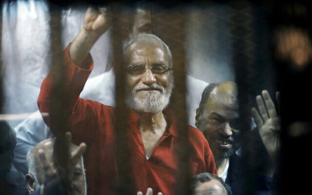Muslim Brotherhood spiritual leader Mohammed Badie waves from a defendants cage in a makeshift courtroom at the national police academy, in eastern Cairo, Egypt, May 16, 2015. (Ahmed Omar/AP)