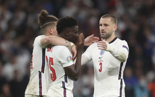 England's Kalvin Phillips, left, and Luke Shaw, right, comfort teammate Bukayo Saka after he failed to score a penalty during a penalty shootout after extra time at the Euro 2020 soccer championship final match between England and Italy at Wembley stadium in London, Sunday, July 11, 2021. (Carl Recine/Pool Photo via AP)