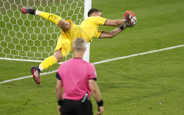Italy's goalkeeper Gianluigi Donnarumma saves a penalty by England's Jadon Sancho during a penalty shootout at the Euro 2020 soccer championship final between England and Italy at Wembley stadium in London, Sunday, July 11, 2021. (John Sibley/Pool Photo via AP)