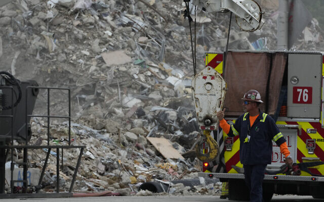 Crews work in the rubble of the demolished section of the Champlain Towers South building, as removal and recovery work continues at the site of the partially collapsed condo building, on  July 12, 2021, in Surfside, Florida (AP Photo/Rebecca Blackwell)