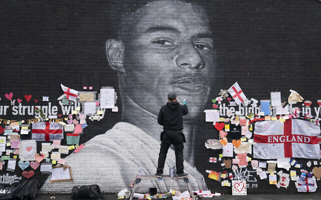 Street artist Akse P19 repairs the mural of Manchester United striker and England player Marcus Rashford on the wall of the Coffee House Cafe on Copson Street, in Withington, Manchester, England, July 13, 2021. (AP/Jon Super)