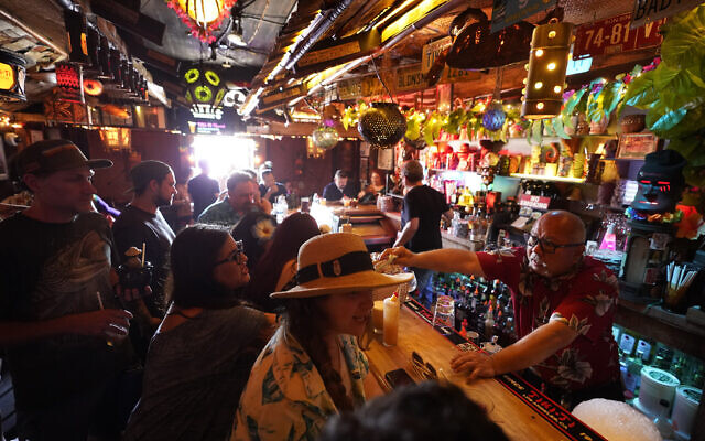 In this Wednesday, July 7, 2021, file photo, patrons enjoy cold tropical cocktails in the tiny interior of the Tiki-Ti bar as it reopens on Sunset Boulevard in Los Angeles. COVID-19 cases have doubled over the past three weeks, driven by the fast-spreading delta variant, lagging vaccination rates in some states and Fourth of July gatherings.  Los Angeles County public health officials have urged people to resume wearing masks indoors regardless of their vaccination status. (AP Photo/Damian Dovarganes, File)