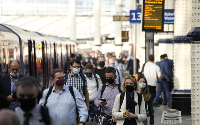People wear face masks to curb the spread of coronavirus as they disembark from a train during the morning rush hour at Waterloo train station in London, Wednesday, July 14, 2021.  (AP Photo/Matt Dunham)