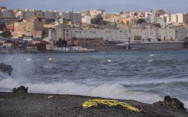 The body of a young man covered with an emergency blanket after being recovered by Spanish police from waters near the border between Morocco and Spain's north African enclave of Ceuta, May 20, 2021. (AP Photo/Bernat Armangue, File)
