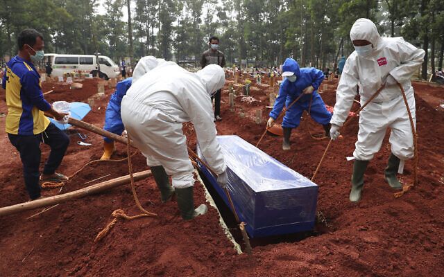 Workers in protective gear lower a coffin of a COVID-19 victim to a grave for burial at the Cipenjo Cemetery in Bogor, West Java, Indonesia, July 14, 2021. (Achmad Ibrahim/AP)