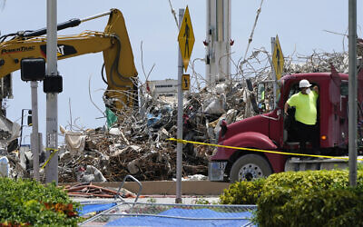 A worker waits to load his truck with debris from the rubble of the Champlain Towers South building, as removal and recovery work continues at the site of the partially collapsed condo building on July 14, 2021, in Surfside, Florida. (AP Photo/Lynne Sladky)