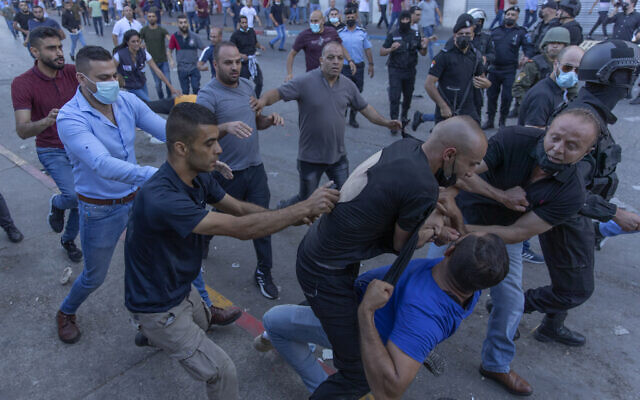 Plainclothes Palestinian security officers detain a protester during clashes that erupted during a demonstration against the death of Nizar Banat, a critic of the Palestinian Authority, in the West Bank city of Ramallah, on June 26, 2021. (AP Photo/Nasser Nasser)
