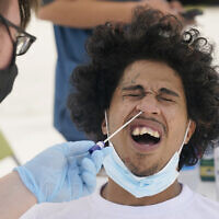 Benny Luna, gets a COVID-19 test from Roberto Gomez, Thursday, July 15, 2021, in Miami. Florida's COVID-19 hospitalization numbers are again increasing, ending months of steady decline that began when widespread vaccinations became available and creating a trend that has epidemiologists worried as the more infectious Delta variant spreads. (AP Photo/Marta Lavandier)