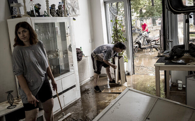 Homeowners push mud and water out of their house after flooding in Angleur, Province of Liege, Belgium, July 16, 2021 (AP Photo/Valentin Bianchi)