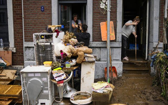 People pass damaged belongings out of a house after flooding in Ensival, Verviers, Belgium, July 16, 2021 (AP Photo/Francisco Seco)