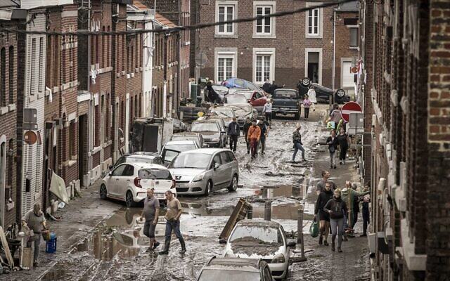 People walk through a damaged street after flooding in Chenee, Province of Liege, Belgium, July 16, 2021 (AP Photo/Valentin Bianchi)