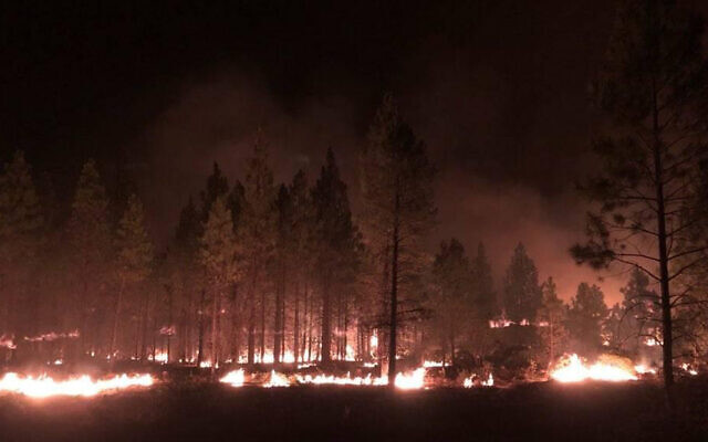 In this photo provided by the Bootleg Fire Incident Command, the Bootleg Fire burns at night near Highway 34 in southern Oregon on July 15, 2021 (Jason Pettigrew/Bootleg Fire Incident Command via AP)