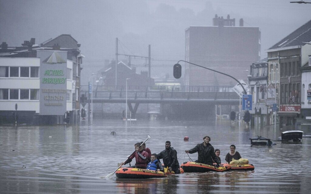 People use rubber rafts in floodwaters after the Meuse River broke its banks during heavy flooding in Liege, Belgium, July 15, 2021 (AP Photo/Valentin Bianchi)