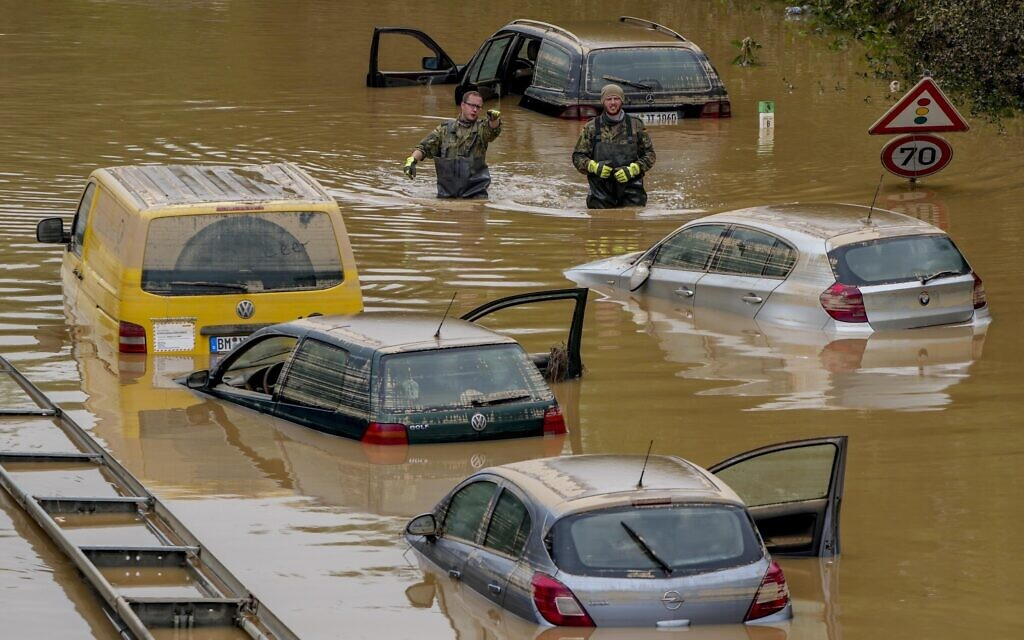 Rescuers check for victims in flooded cars on a road in Erftstadt, Germany, on July 17, 2021. (AP Photo/Michael Probst)