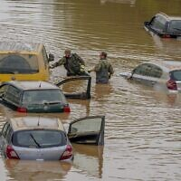 Rescuers check for victims in flooded cars on a road in Erftstadt, Germany,  July 17, 2021 (AP Photo/Michael Probst)