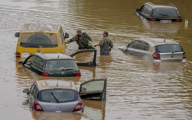 Rescuers check for victims in flooded cars on a road in Erftstadt, Germany, July 17, 2021 (AP/Michael Probst)