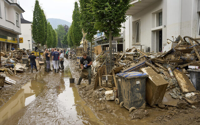Residents clear mud and unusable furniture from houses in the city center of Bad Neuenahr, western Germany, on July 17, 2021. (Thomas Frey/dpa via AP)
