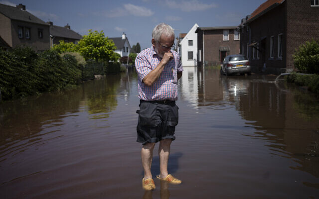 Wiel de Bie, 75, stands outside his flooded home in the town of Brommelen, Netherlands, on July 17, 2021. (AP Photo/Bram Janssen)