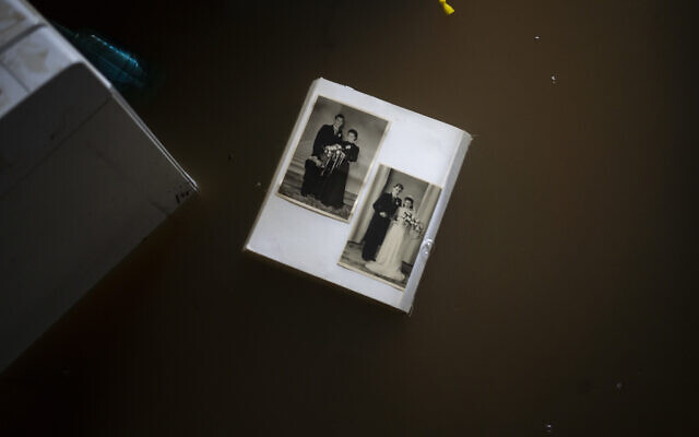 Wedding photos float in water in a flooded basement of a home, in the town of Brommelen, Netherlands, on July 17, 2021. (AP Photo/Bram Janssen)