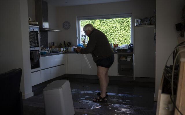 Ijmert Kant assesses the damage in his home in the town of Brommelen, Netherlands, on July 17, 2021. (AP Photo/Bram Janssen)