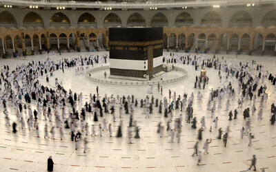 Muslim pilgrims circumambulate the Kaaba, the cubic building at the Grand Mosque, as they wear masks and keep social distancing, a day before the annual hajj pilgrimage, on July 17, 2021. (AP Photo/Amr Nabil)