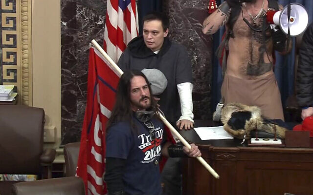 In this file image from US Capitol Police video, Paul Allard Hodgkins, 38, of Tampa, Fla., front, stands in the well on the floor of the US Senate on Jan. 6, 2021, at the Capitol in Washington. (U.S. Capitol Police via AP)