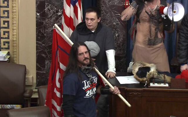 In this file image from US Capitol Police video, Paul Allard Hodgkins, 38, of Tampa, Florida, front, stands in the well on the floor of the US Senate on Jan. 6, 2021, at the Capitol in Washington. (U.S. Capitol Police via AP, File)