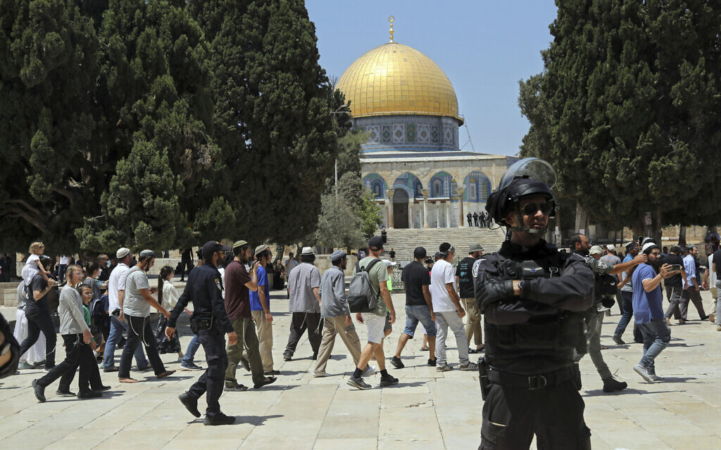 An Israeli police officer stands guard as a Jewish group walks near the Dome of the Rock Mosque atop the Temple Mount on Tisha B'Av (the ninth of Av), a day of fasting commemorating the destruction of the ancient Temples, in the Old City of Jerusalem, Sunday, July 18, 2021. (AP Photo/Mahmoud Illean)