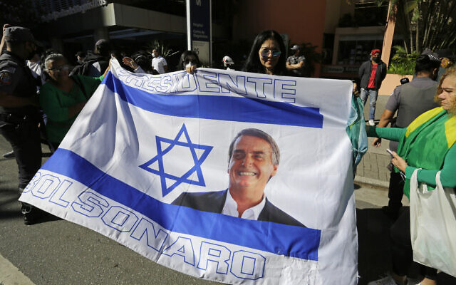 Supporters of Brazilian President Jair Bolsonaro holds an Israeli flag with the image of Bolsonaro, on it as they wait in front of a hospital where Bolsonaro is recovering from an intestinal obstruction in Sao Paulo, Brazil, on July 18, 2021. (AP Photo/Nelson Antoine)