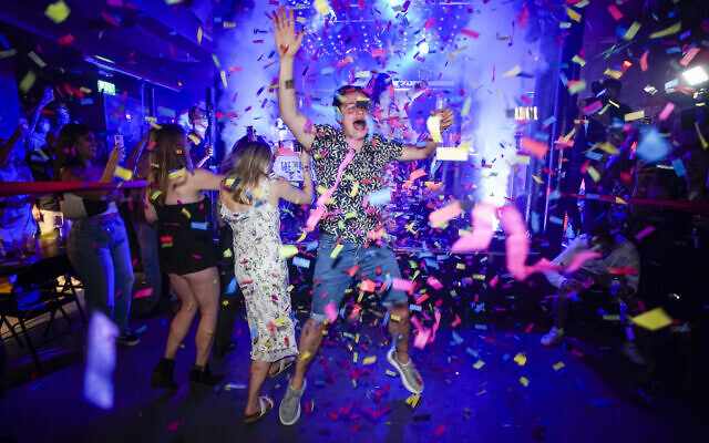 A man jumps on the dance floor shortly after the reopening, at The Piano Works in Farringdon, in London, Monday, July 19, 2021. The country's nightclubs are reopening for the first time in 17 months as almost all coronavirus rules are set to be scrapped. (AP Photo/Alberto Pezzali)