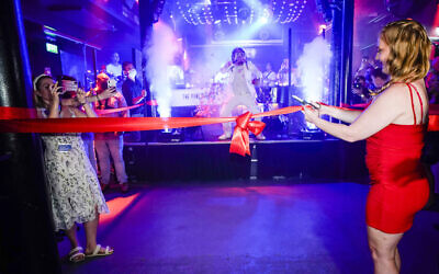 A woman cuts the ribbon on the dance floor of The Piano Works in Farringdon, in London, Monday, July 19, 2021. Thousands of young people plan to dance the night away at 'Freedom Day' parties after midnight Sunday, when almost all coronavirus restrictions in England are to be scrapped. Nightclubs, which have been shuttered since March 2020, can finally reopen. (AP Photo/Alberto Pezzali)