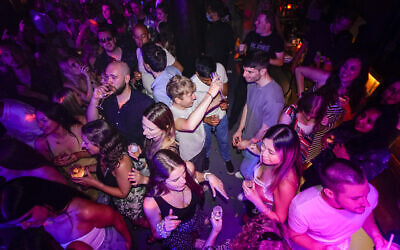 People drink on the dance floor shortly after the reopening, at The Piano Works in Farringdon, in London, Monday, July 19, 2021. Thousands of young people plan to dance the night away at 'Freedom Day' parties after midnight Sunday, when almost all coronavirus restrictions in England are to be scrapped. Nightclubs, which have been shuttered since March 2020, can finally reopen. (AP Photo/Alberto Pezzali)