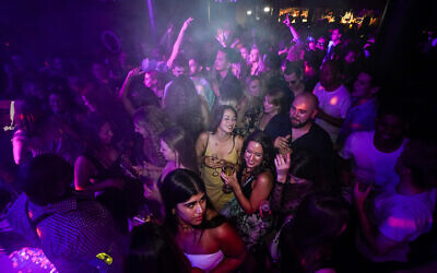 People drink on the dance floor shortly after the reopening, at The Piano Works in Farringdon, in London, Monday, July 19, 2021. (AP Photo/Alberto Pezzali)
