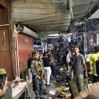 People and security forces gather at the site of a bombing in Wahailat market in Sadr City, Iraq, July 19, 2021. (AP Photo/ Khalid Mohammed)