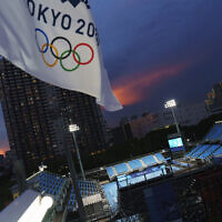 An Olympic flag flies above the Ariake Tennis Center at the 2020 Summer Olympics, on Tuesday, July 20, 2021, in Tokyo. (AP Photo/David Goldman)