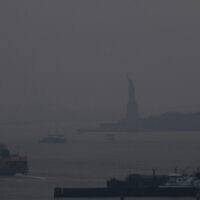 The Staten Island Ferry departs from the Manhattan terminal through a haze of smoke with the Statue of Liberty barely visible, Tuesday, July 20, 2021, in New York. (AP Photo/Julie Jacobson)