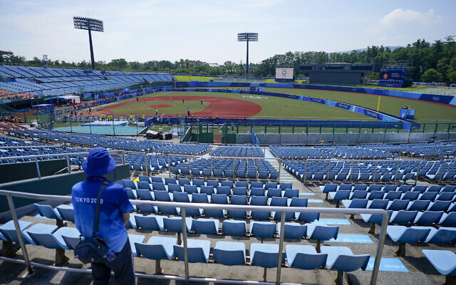 A steward watches from the empty grandstands during the softball game between Japan and Australia at the 2020 Summer Olympics, July 21, 2021, in Fukushima, Japan. (AP/Jae C. Hong)
