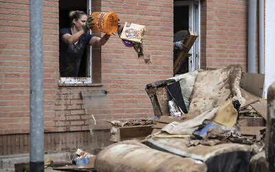 A woman throws rubbish from the window of her home onto a pile of discarded goods in the district of Blessem, in Ergfstadt, Germany, Thursday July 22, 2021.  In the flood disaster area of Erftstadt-Blessem, some residents are being allowed back into their homes to clear debris after heavy rains caused devastating floods. (Marius Becker/dpa via AP)