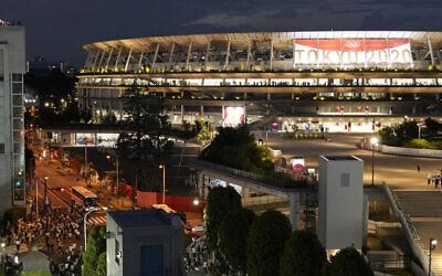 Protesters, left bottom, gather outside the National Stadium, before the opening ceremony starts at the 2020 Summer Olympics, July 23, 2021, in Tokyo. (AP Photo/Shuji Kajiyama)