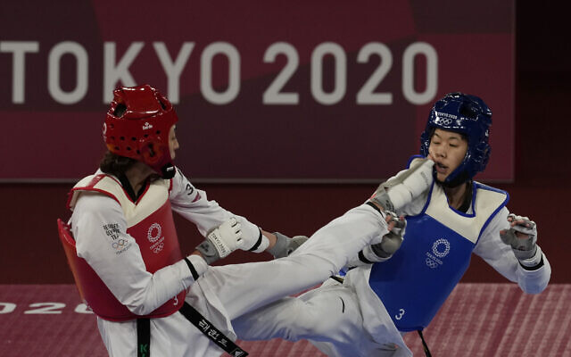 Kimia Alizadeh Zonoozi, Refugee Olympic Team, left, attacks China's Zhou Lijun during the taekwondo women's 57kg match at the 2020 Summer Olympics, July 25, 2021, in Tokyo, Japan. (AP Photo/Themba Hadebe)