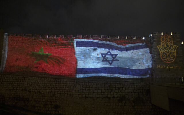 """The national flags of Israel and Morocco are projected on the walls of the Old City of Jerusalem, along with the word """"peace,"""" in English, Hebrew, and Arabic,  December 23, 2020. (AP Photo/Maya Alleruzzo, File)"""