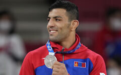 Saeid Mollaei of Mongolia celebrates with his silver medal during the award ceremony for the men -81kg judo match at the 2020 Summer Olympics in Tokyo, Japan, Tuesday, July 27, 2021. (AP Photo/Vincent Thian)