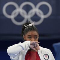 Simone Biles, of the United States, watches gymnasts perform at the 2020 Summer Olympics in Tokyo, July 27, 2021. (Ashley Landis/AP)