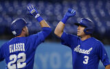 Israel's Ian Kinsler celebrates with Mitchell Glasser after hitting a home run in the third inning of a baseball game against South Korea at the 2020 Summer Olympics, July 29, 2021, in Yokohama, Japan. (AP Photo/Sue Ogrocki)