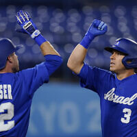 Israel's Ian Kinsler celebrates with Mitchell Glasser after hitting a home run in the third inning of a baseball game against South Korea at the 2020 Summer Olympics, on July 29, 2021, in Yokohama, Japan. (AP Photo/Sue Ogrocki)