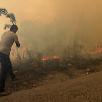 A man tries to extinguish g a forest fire, at Qobayat village, in the northern Akkar province, Lebanon, July 29, 2021. (Hussein Malla/AP)