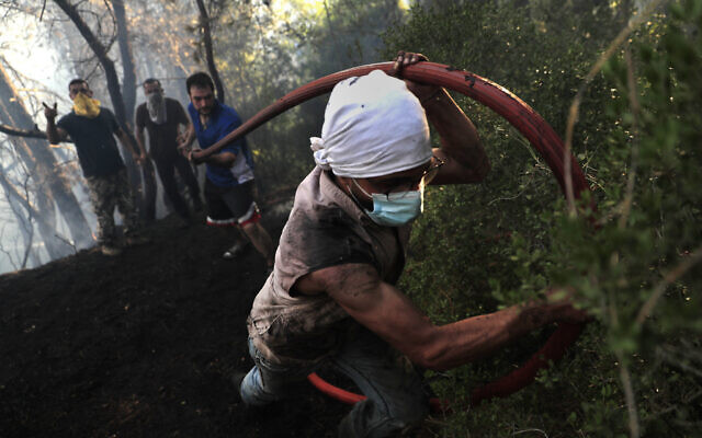 Civil defense workers extinguish a forest fire, at Qobayat village, in the northern Akkar province, Lebanon, on Thursday, July 29, 2021. (AP Photo/Hussein Malla)